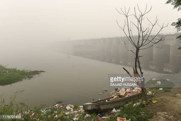 A boat is seen amidst heavy smog conditions surrounded by rubbish near a bridge along the Yamuna River in New Delhi on November 3 2019 India's...