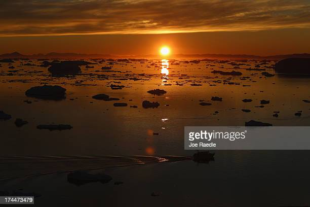 Boat is seen seen among the icebergs that broke off from the Jakobshavn Glacier as the sun reaches its lowest point of the day on July 23, 2013 in...