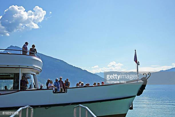 Boat just arrived at Spiez landing pier People enjoy view across Lake Thun towards Mount Beatenberg Bernese Oberland Region Switzerland
