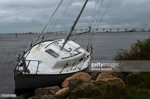 Boat lays on the rocks after the passing of Hurricane Matthew in Titusville, Florida on October 7, 2016. Fierce Hurricane Matthew left behind...