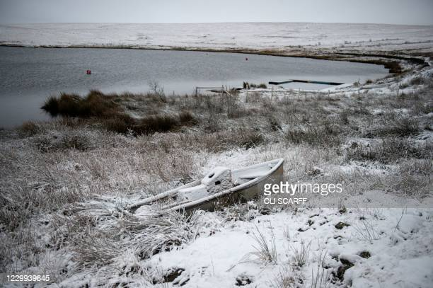 Boat lies covered in snow at the edge of Redbrook Reservoir above the village of Marsden, near Manchester in northern England on December 4, 2020.