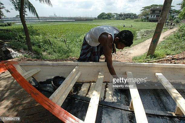 A boat maker giving coats of bitumen on the bottom of a newly made boat Demra Dhaka Bangladesh July 6 2005