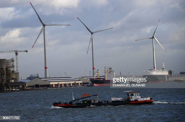 A boat makes its way past wind turbines in the Port of Antwerp on January 17 2018 / AFP PHOTO / EMMANUEL DUNAND
