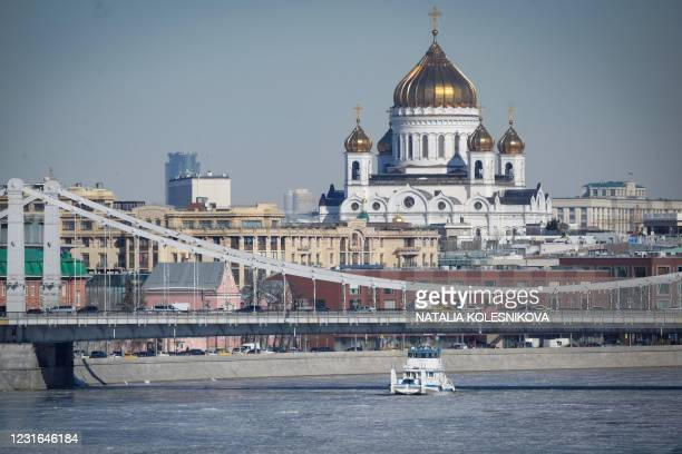 Boat makes its way through ice floes on the Moskva river in front of the Cathedral of Christ the Saviour in Moscow on March 11, 2021.