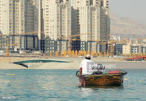 CONTENT] Boat man in Chitgar artificial lake contemplates the rapid urban growth of Western Tehran