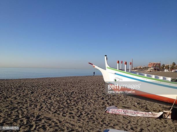 boat moored at beach against clear blue sky - muro stock photos and pictures