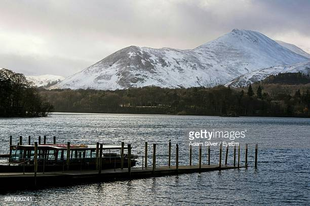 Boat Moored At Lake Against Snow Covered Mountains