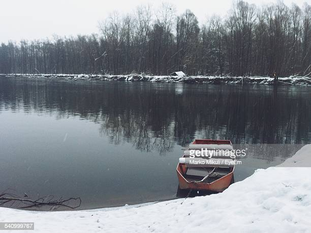 Boat Moored At Snowcapped Lakeshore During Winter