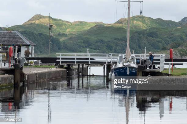 Boat moored at the sea locks from Loch Crinan and the entrance to the Crinan Canal on August 19, 2021 in Crinan, Scotland. Passage along the canal...