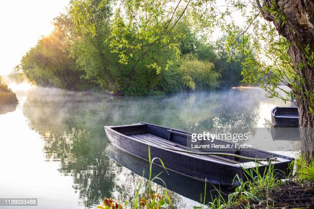 boat moored by lake against trees - bourges imagens e fotografias de stock