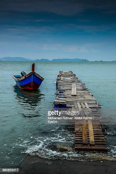 Boat Moored By Old Pier Over Sea