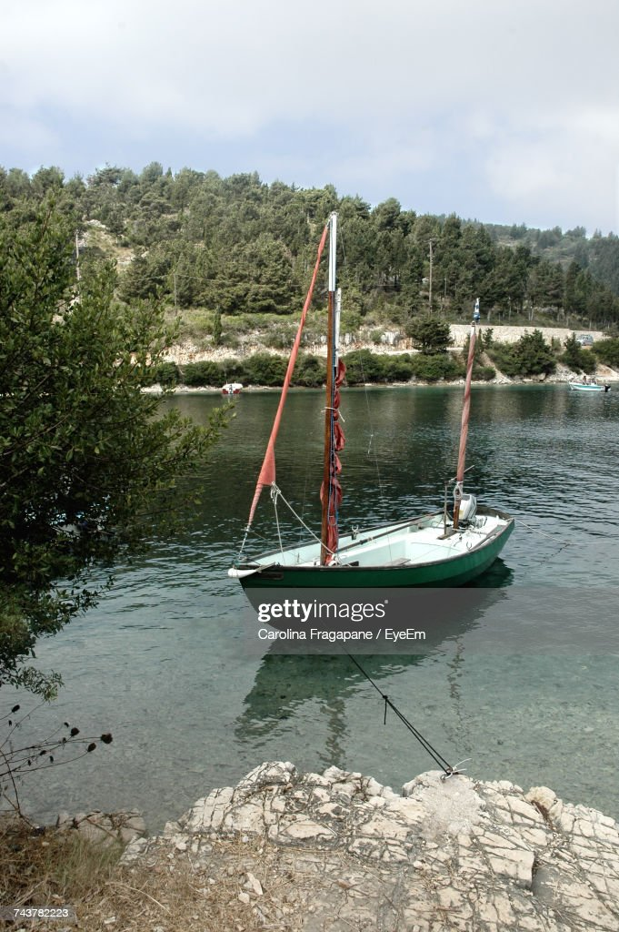 Boat Moored By Trees Against Sky : Foto stock