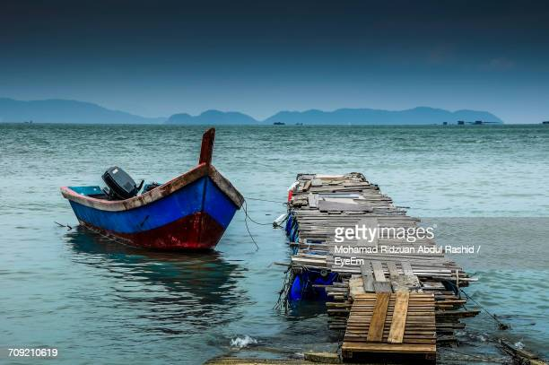 Boat Moored By Wooden Jetty In Sea Against Sky