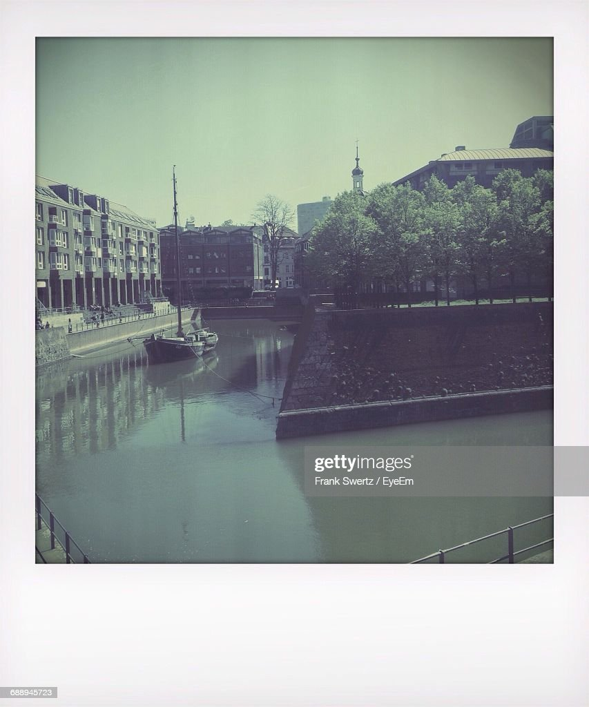 Boat Moored In Canal Against Buildings : Stock-Foto
