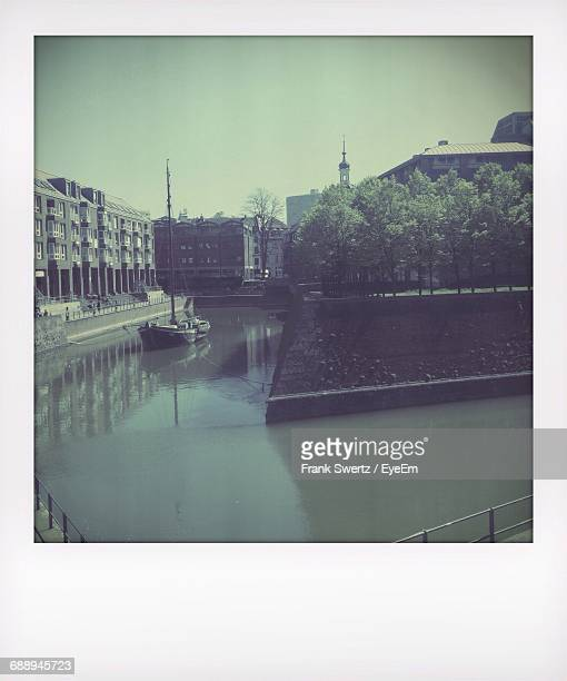 boat moored in canal against buildings - frank swertz stockfoto's en -beelden
