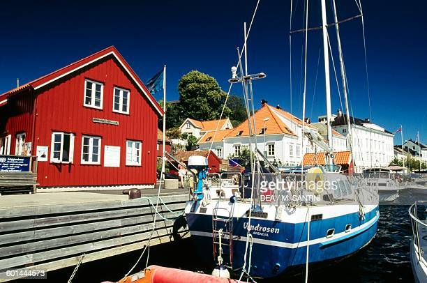 Boat moored in front of the traditional houses in Arendal AustAgder County Norway