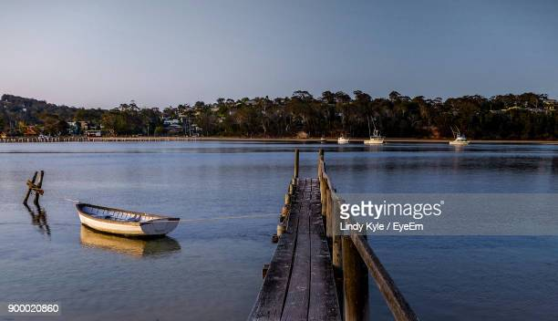 boat moored in lake against clear sky - merimbula stock pictures, royalty-free photos & images