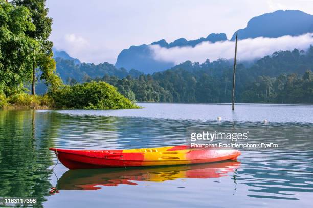 boat moored in lake against mountains - surat thani province stock pictures, royalty-free photos & images