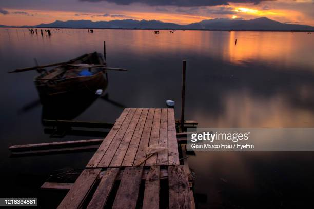 boat moored in lake against sky during sunset - frau photos et images de collection