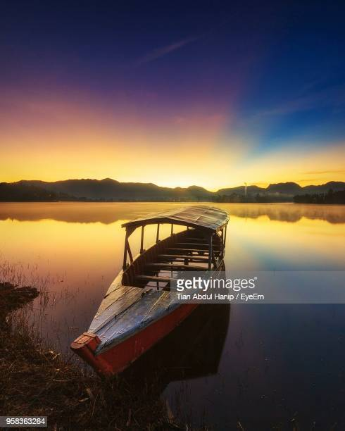 boat moored in lake against sky during sunset - tian abdul hanip stock photos and pictures