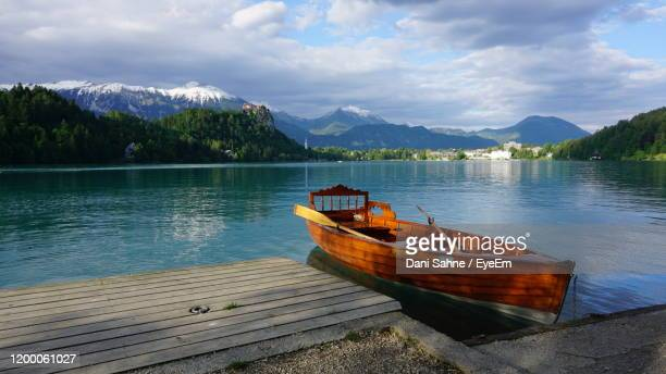 boat moored in lake against sky - sahne ストックフォトと画像