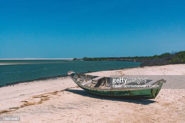 boat moored on beach against clear blue sky - barreirinhas stock pictures, royalty-free photos & images