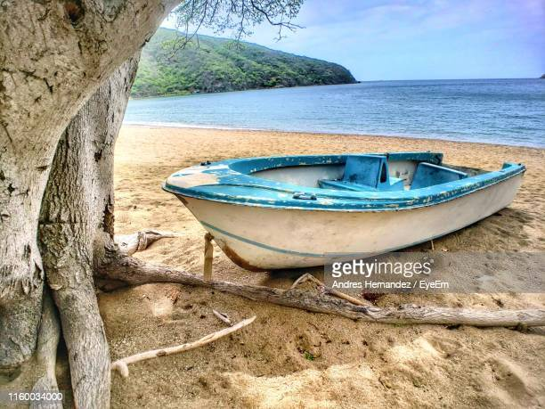 boat moored on beach against sky - recreational boat stock pictures, royalty-free photos & images