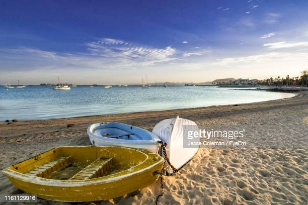 boat moored on beach against sky - jesse coleman stock pictures, royalty-free photos & images