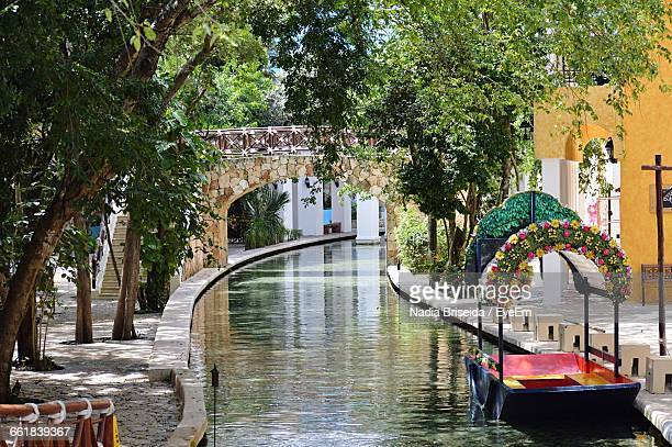 boat moored on canal in theme park - monterrey stock photos and pictures