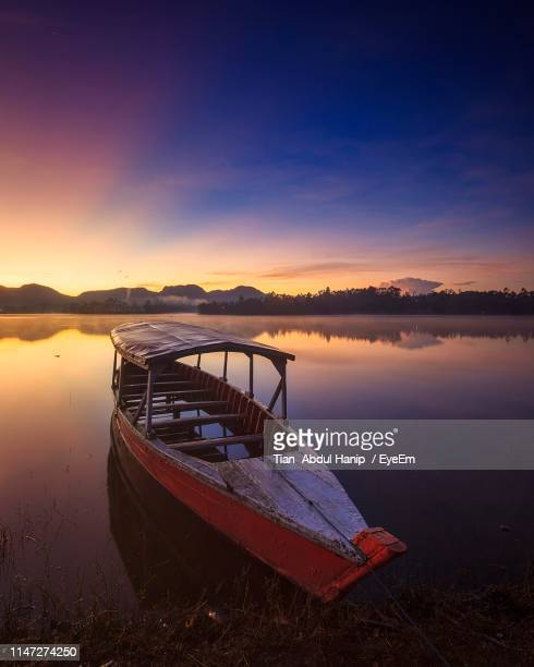 boat moored on lake against sky during sunset - tian abdul hanip stock photos and pictures
