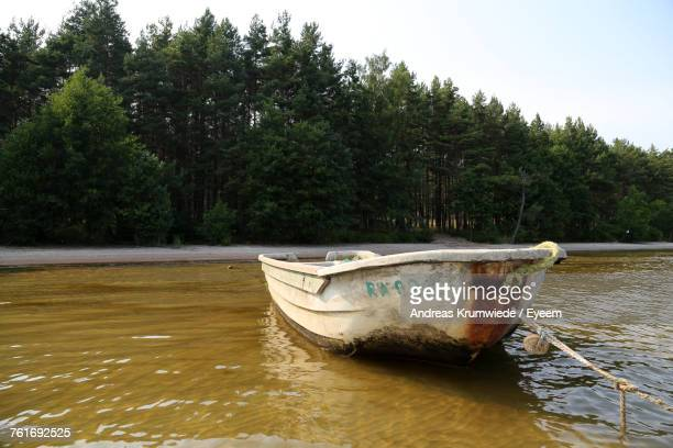Boat Moored On Lake By Trees Against Sky