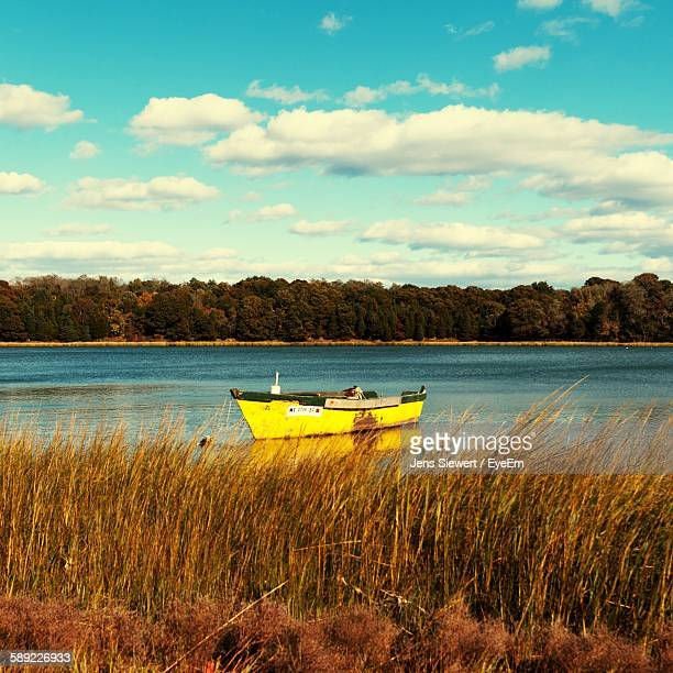 boat moored on river by trees against sky - jens siewert stock-fotos und bilder