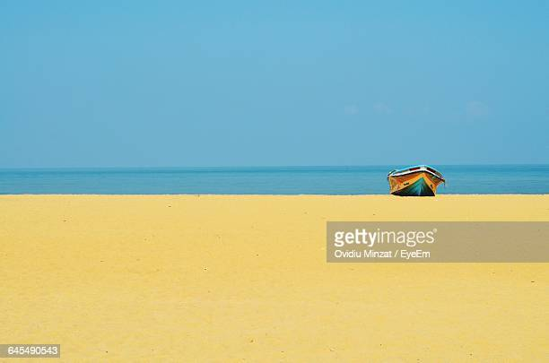 Boat Moored On Shore At Beach Against Blue Sky