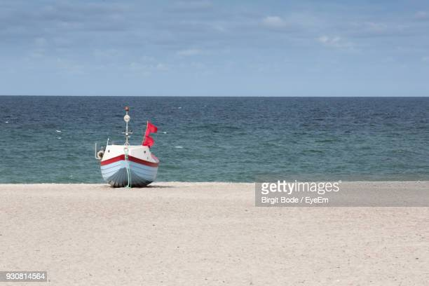 Boat Moored On Shore At Beach Against Sky