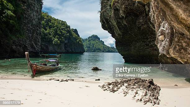 boat moored on shore by rock formations - asia carrera imagens e fotografias de stock