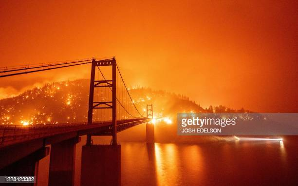 Boat motors by as the Bidwell Bar Bridge is surrounded by fire in Lake Oroville during the Bear fire in Oroville, California on September 9, 2020. -...