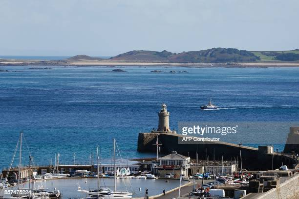 Boat motors into the island of Guernsey in the Channel Islands on October 3, 2017. / AFP PHOTO / CHARLY TRIBALLEAU