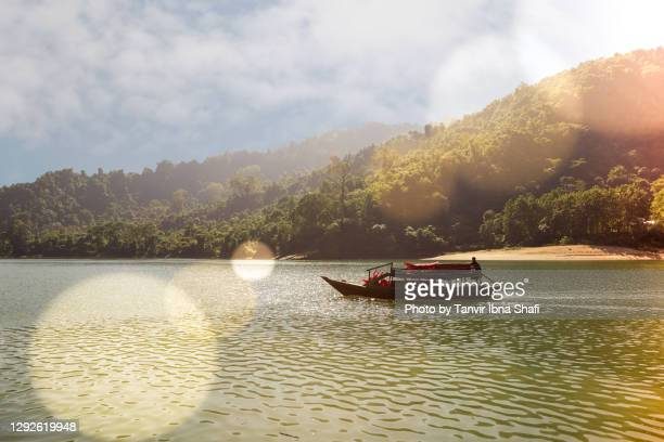 boat moving through narrow river and mountains on a sunny day - river stock pictures, royalty-free photos & images