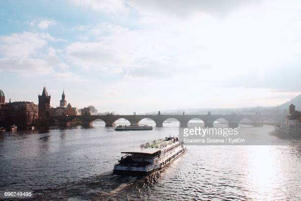 boat moving towards charles bridge in vltava river against cloudy sky - vltava river stock photos and pictures