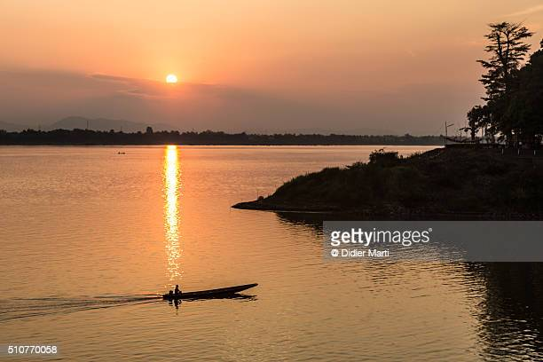 a boat navigating on the mekong in laos - didier marti stock photos and pictures