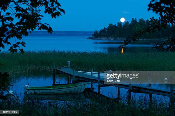 boat near jetty at night - dalsland stock photos and pictures