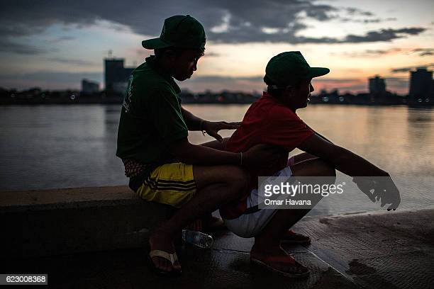 A boat oarsman gives a massage to a teammate before training on the first day of the Water Festival on November 13 2016 in Phnom Penh Cambodia The...