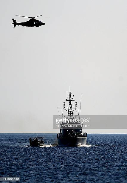 A boat of migrants coming from Tunisia is escorted by an Italian helicopter and a coast guards boat upon arrival on the italian island of Lampedusa...