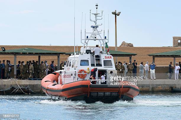A boat of the Coast Guards arrives in the Lampedusa harbour on October 6 2013 after divers recovered ten more bodies from the shipwreck that sank two...