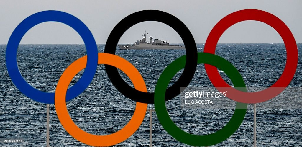 TOPSHOT - A boat of the Navy of Brazil is pictured with the Olympic Rings in the foreground as she patrols the coast of Copacabana beach, in Rio de Janeiro, on August 4, 2016, ahead of the Rio 2016 Olympic Games. / AFP / LUIS