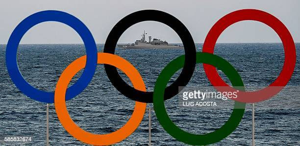 TOPSHOT A boat of the Navy of Brazil is pictured with the Olympic Rings in the foreground as she patrols the coast of Copacabana beach in Rio de...