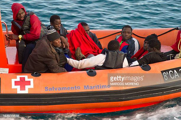 A boat of the Red Cross carries nine wouldbe immigrants rescued off the Spanish coast to the port of Tarifa on March 18 2013 Spanish rescuers...