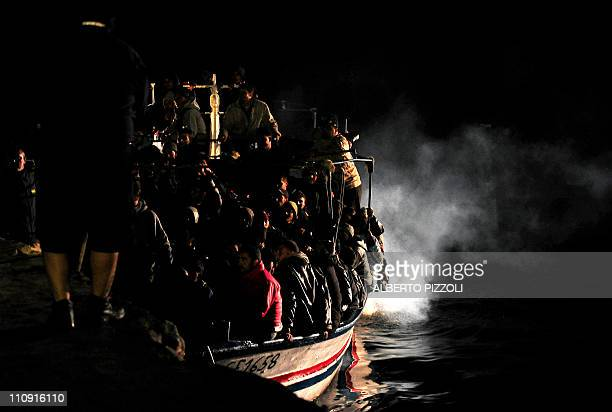 A boat of Tunisian wouldbe immigrants arrives in Lampedusa on March 26 2011 The Italian government says more than 15000 migrants have arrived on the...