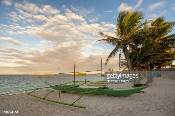 A boat on a beach in Boracay in Philippines later afternoon under palm trees