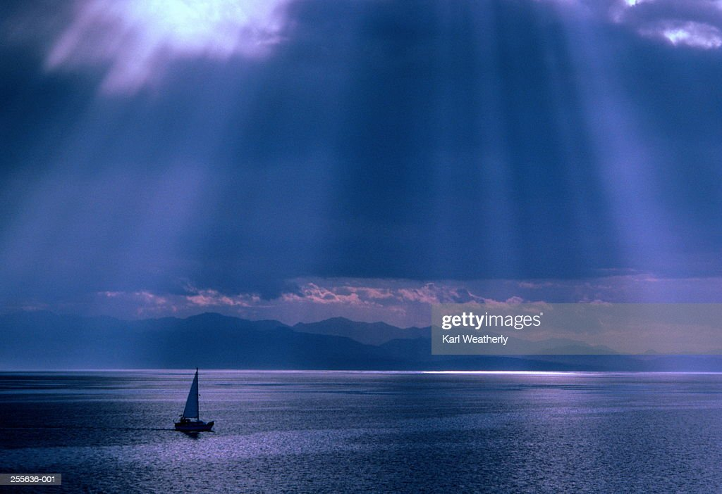 Boat on calm sea,sun breaking through cloud above : Stock Photo